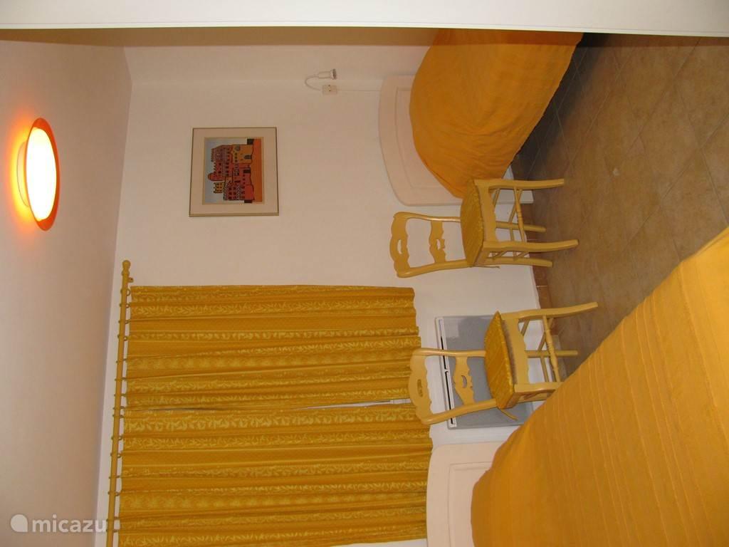 gele slaapkamer met twee eenpersoonsbedden