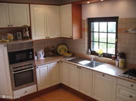 Volledig ingerichte keuken met deur naar het terras en uitzicht op het prachtige Porches.