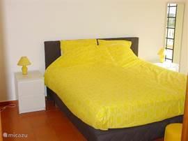 Slaapkamer op de bovenverdieping met dakterras en aangrenzende  badkamer met douche.