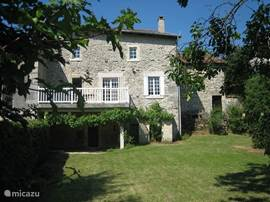 The back of the house with a sunny terrace above the shaded terrace. In the large garden including a swing and a plum and apple.