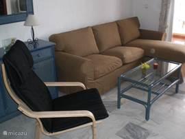 De woonkamer met 3-zitsbank, relax stoel en salontafel