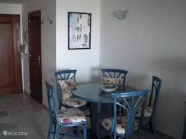 De woonkamer heeft veel licht met de eethoek met vijf stoelen aan de keukenzijde