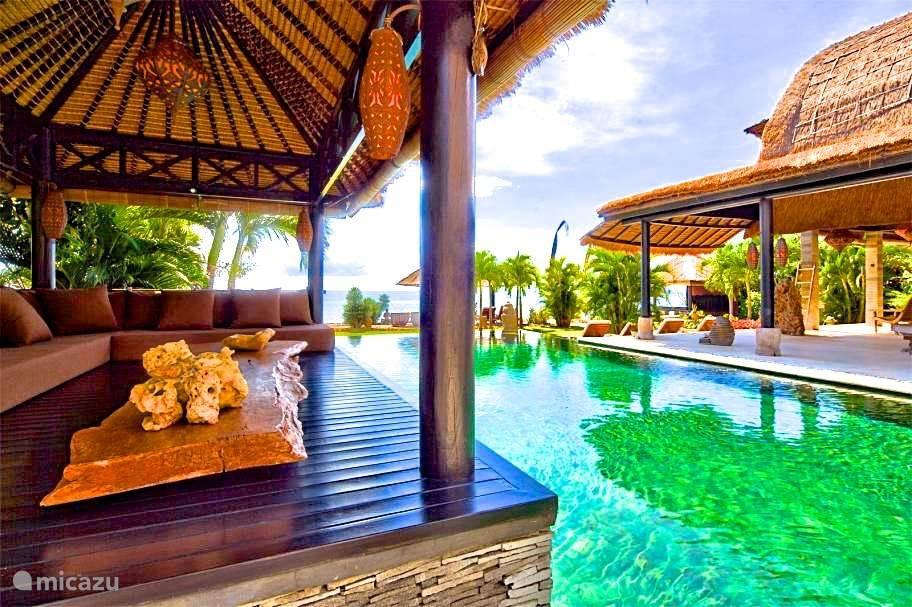 Lounge plek met dikke kussens aan het zwembad van villabuddha