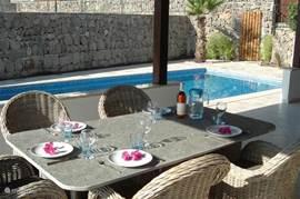 Onder de veranda ( 65m2) is het heerlijk vertoeven. Er staat een grote lounge set met lekkere kussens en ook is er een aparte eettafel met uitzicht over het zwembad.