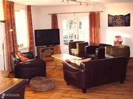woonkamer van 60 vierkante meter met houten vloer en met groot plasma tv scherm (127 cm) en zicht op het kanaal