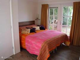De tweede slaapkamer beneden met openslaande tuindeuren en een eigen douche en toilet.Met boxspring.