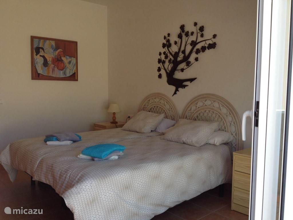 Master bedroom op de 1e etage met schuifpui naar het zonneterras. N.B. naast fan ook airco units beschikbaar overal.