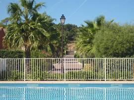 Uitzicht vanuit het zwembad naar het pad en de entree van Green Village