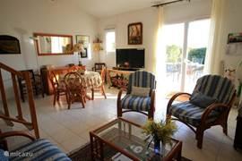 De woonkamer met zithoek en openslaande deur naar het voorterras