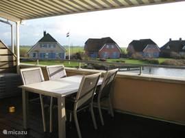 Het grote terras op het zuiden kijkt uit over het luxe vakantiepark en verder de weilanden in.