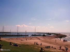 Vanaf het strand kan je zo naar de Frisosluis waar de boten vanaf het IJsselmeer geschut worden om zo via het Frisokanaal, dus vóór ons vakantiehuis langs, de Friese meren op gaan (ook vice versa natuurlijk)  Ook kan je de pier die je hier op de foto ziet, belopen.