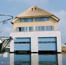 Achterkant van het huis. Ons huis heeft een extra lange aanlegsteiger van 10m. Hier kunt u evt. uw boot aanleggen. Er is een boothelling aanwezig.