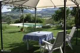 Het zitje onder de pergola biedt op warme dagen beschutting tegen de zon.