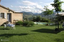 Uitzicht vanuit de tuin van het appartement op het zwembad en de bergen.