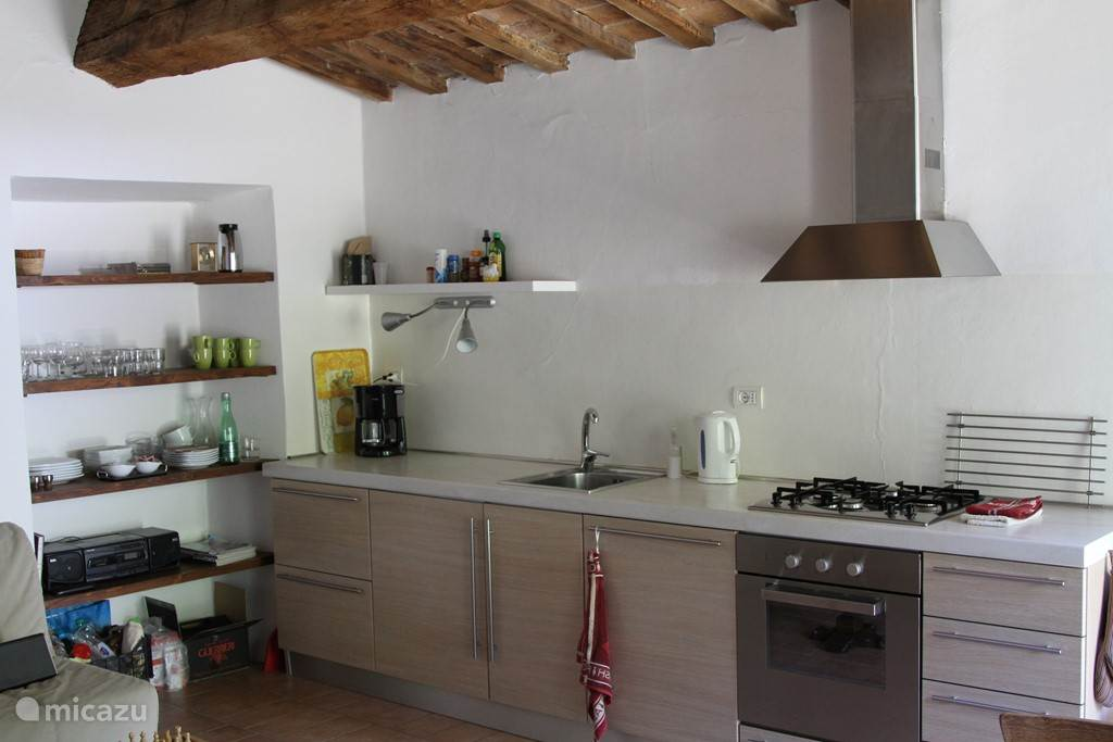 De moderne keuken met alle apparatuur, inclusief vaatwasser, oven en 4-pits gasfornuis.