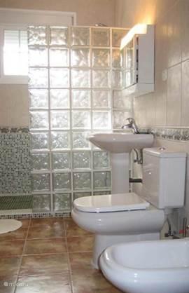 2e badkamer in de woning met inloopdouche, wastafel, bidet en toilet.