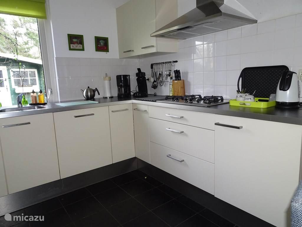 De gezellige, open keuken is compleet ingericht en voorzien van luxe inbouwapparatuur zoals een vaatwasser, koelkast met diepvriesvak, een combimagnetron en een 4-pits gastoestel.
