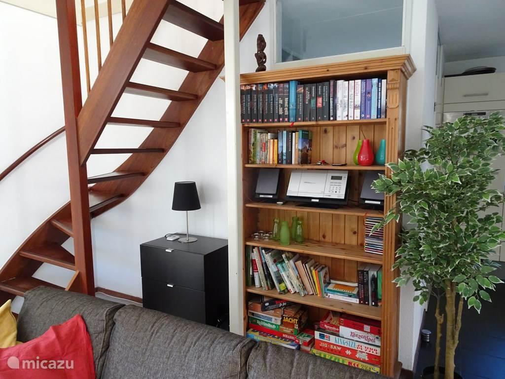 De boekenkast waarin ook veel spelletjes, informatieve natuurboeken en kookboeken te vinden zijn. Links de trap naar de bovenverdieping.