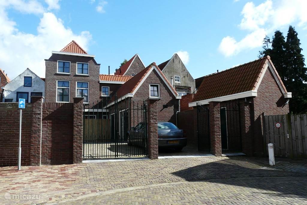 Achterzijde woning met parkeergelegenheid, welke kan worden afgesloten met poorten.