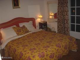 slaapkamer 1,  met openslaande deuren naar terras en uitzicht op zee