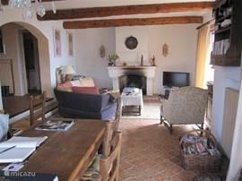 woonkamer vanaf de eettafel gezien naar de openhaard en de t.v. (met o.a. enkele ned. zenders)