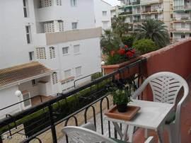 Balkon met zitje. Er zijn meer buitenstoelen. In de namiddag komt de zon op het balkon.