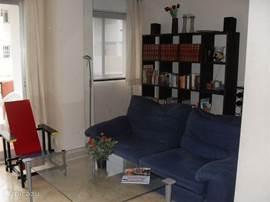 Zicht naar het balkon en de boekenkast met Nederlandse en Engelse boeken.