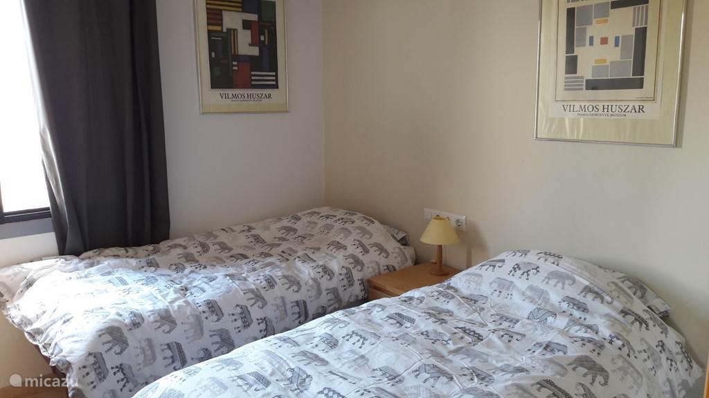 Slaapkamer met twee (onderschuif) éénpersoonsbedden. Niet zichtbaar: een ladenkast en het openslaande raam.