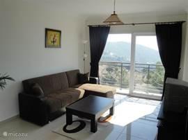Uitzicht vanaf woonkamer over heuvels met cypressen en olijfbomen.