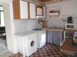 Een volledig ingerichte keuken met o.a. een magnetron, wasmachine, afwasmachine.
