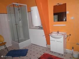 De badkamer met douche, wastafel en toilet. Handdoeken zijn aanwezig.
