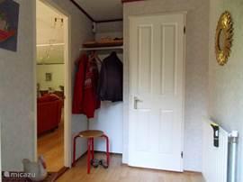 Entree met garderobe waarachter een bezemkast en de cv-installatie. Deuren naar woonkamer, tweede slaapkamer en toilet.