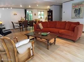 Huiskamer van ruim 50 m2, gezellig ingericht met comfortabele bank en feauteuils. Achter in de hoek de open keuken.