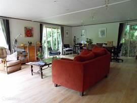 Woon/zitkamer met achterin een apart zitje. De vloer is licht eiken laminaat.