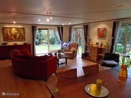 Een gezellige ruime kamer waar het goed toeven is, met een fijne bank, lekkere fauteuils. Tv, dvd, radio/cd en diverse spellen waaronder een sjoelbak.