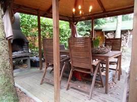 Prieel met houten tuinset en open haard.