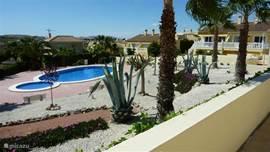 Zicht op de mooi aangelegde tuin met het zoutwater zwembad. Het tweede huis van rechts (met het trapje) is Casa Dorada.