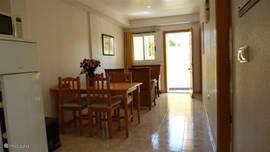 De woonkamer op de onderste woonlaag, voorzien van een bankstel, eettafel voor 4 personen.
