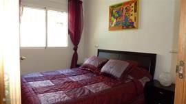De slaapkamer op de bovenste woonlaag met het 2 persoons bed, voorzien van airco (warm en koud) en inbouwkast met zowel hang- als leggedeelte.