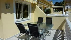 Een gedeelte van het terras dat voorzien is van een tafel met verstelbare stoelen en een zonnescherm. Aan de zijkant van het terras is een trapje waardoor u direct in de tuin aan de voorkant van het huis en de beneden verdieping komt.