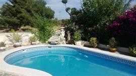 vanaf het zwembad met waterval uitzicht  over de omgeving, het dorp , wijngaarden en bergen