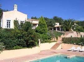 De Quinta gezien vanaf het zwembad.Tegen het talud groeien/bloeien vele planten en 2 sinaasappelboombjes.