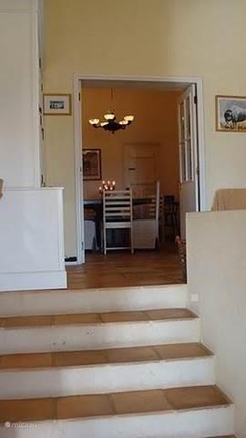 Overloop van eetkamer naar de iets lager gelegen zitkamer.Hier staat de boekenkast . Er is daar een deur naar de veranda.