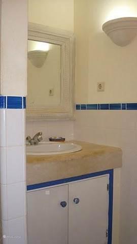 deel badkamer van de blauwe vloer met mooie rand om de spiegel.Achter de muur is de douche en op zij het toilet .