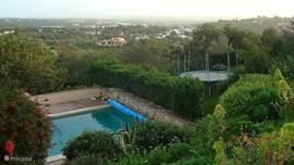 Zwembad ook van boven gezien richting speelveld met de trampoline.